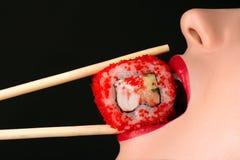 Menina 'sexy' que come o rolo de sushi, bordos vermelhos sensuais foto de stock royalty free