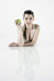 Menina 'sexy' que encontra-se no assoalho com uma maçã Fotos de Stock Royalty Free