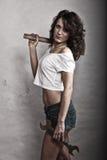 Menina 'sexy' que guarda a chave inglesa do martelo e da chave Fotografia de Stock Royalty Free