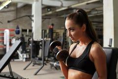 Menina 'sexy' que levanta ao exercitar no gym Fotografia de Stock Royalty Free