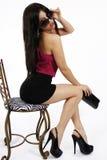 Menina 'sexy' que senta-se em uma cadeira foto de stock