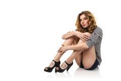 Menina 'sexy' que senta-se no assoalho fotografia de stock royalty free