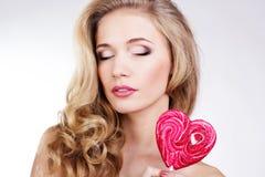 Menina 'sexy' que veste o vestido cor-de-rosa com doces. Imagens de Stock