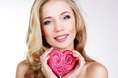 Menina 'sexy' que veste o vestido cor-de-rosa com doces. Fotografia de Stock
