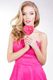 Menina 'sexy' que veste o vestido cor-de-rosa com doces Foto de Stock