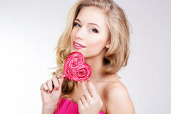 Menina 'sexy' que veste o vestido cor-de-rosa com doces Foto de Stock Royalty Free
