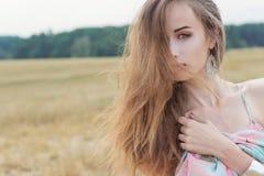 A menina 'sexy' ruivo bonita em sundress brilhantes do verão com bordos grandes plump o campo de ação Fotografia de Stock Royalty Free