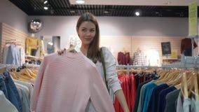 A menina shopaholic bonita escolhe a roupa à moda nova e a tentativa na frente do espelho no boutique da forma durante descontos  filme