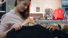 A menina shopaholic de sorriso escolhe a roupa nova em ganchos e a tentativa nsi mesmo na loja da forma durante descontos na alam video estoque