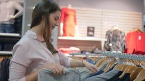 A menina shopaholic de sorriso feliz escolhe a roupa à moda nova e os olhares no espelho no boutique da forma durante descontos d vídeos de arquivo