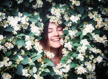 A menina smilling nova feliz que tem o divertimento trava as pétalas com suas mãos no fundo do arbusto de florescência com as flo fotografia de stock royalty free