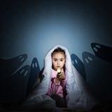 Menina sob as tampas com uma lanterna elétrica Imagem de Stock Royalty Free