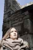 Menina sob uma parede de pedra Imagens de Stock