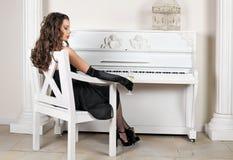 A menina sobre o piano imagem de stock