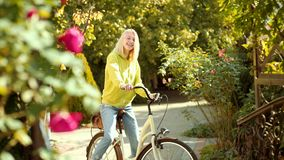 A menina sonhadora com cabelo louro na camiseta da malha está montando a bicicleta no parque Jovem mulher romântica na mola vídeos de arquivo