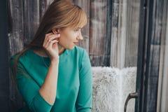 A menina sonhadora do retrato em um vestido verde olha para fora a janela foto de stock royalty free