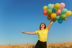 Menina sonhadora que salta altamente com grupo dos balões fotos de stock royalty free