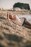 A menina sonhadora relaxa na praia em camisas das calças de brim da forma Fotografia de Stock