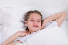 a menina sonolento na cama, abre seus olhos e puxa-se para o lado para acordar foto de stock royalty free
