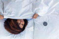 Menina sonolento que olha o despertador ao descansar na cama fotografia de stock