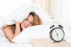 Menina sonolento que olha o despertador e que tenta esconder sob fotografia de stock