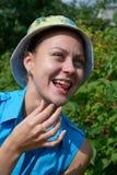 A menina sorri em um jardim com framboesa Foto de Stock