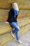 A menina sorri perto de uma cabana do registro Imagem de Stock Royalty Free