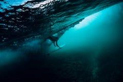 A menina sozinha do surfista com prancha faz o mergulho do pato subaquático com a onda de oceano grande fotografia de stock royalty free