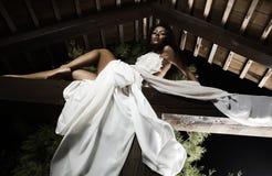 Menina suntanned atrativa nos poses brancos do vestido. Foto de Stock