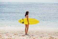 Menina surfando da mulher do surfista que anda guardando a prancha Conceito do curso das férias de verão do esporte de água imagem de stock