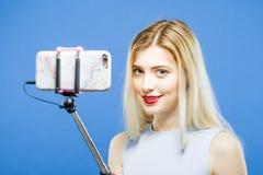 Menina surpreendente com cabelo longo e os bordos vermelhos que fotografa-se por Smartphone no estúdio O louro bonito fizer caret Fotografia de Stock Royalty Free