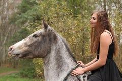 Menina surpreendente com o cabelo longo que monta um cavalo Fotografia de Stock