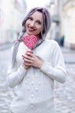 Menina surpreendente do retrato do close up na camiseta de lã morna branca com cabelo de prata cinzento com o pirulito vermelho e Imagem de Stock Royalty Free