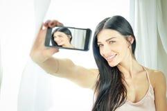 Menina surpreendente encantador no camisole que faz o selfie foto de stock royalty free