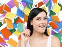 A menina surpreendente está pensando sobre a educação e está indicando seu dedo acima Livros coloridos no fundo Foto de Stock