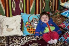 Menina surpreendente que senta-se na cama em uma cama com descansos bordados imagens de stock royalty free