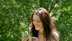 A menina surpreendente ri a mensagem da leitura na rede social em seu telefone celular Retrato do close up da mulher moreno bonit video estoque
