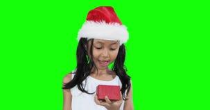 A menina surpreendida abre um presente do Natal video estoque