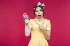Menina surpreendida bonito do pinup que aponta no despertador Imagem de Stock