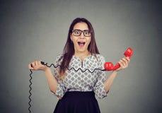 Menina surpreendida com o receptor vermelho do telefone imagem de stock