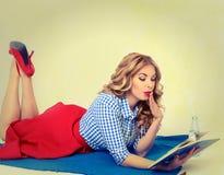 Menina surpreendida com um livro à disposição retro Imagem de Stock Royalty Free