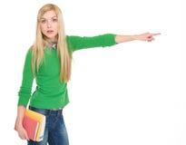 Menina surpreendida do estudante que aponta no espaço da cópia Imagem de Stock