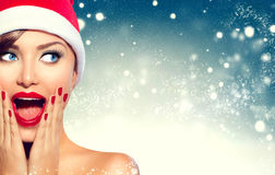 Menina surpreendida do Natal Mulher da beleza no chapéu do ` s de Santa fotografia de stock