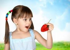 Menina surpreendida engraçada da criança com morango foto de stock