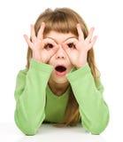 A menina surpreendida está mostrando o gesto dos vidros foto de stock royalty free