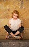A menina surpreendida levanta-se acima por suas pontas do dedo Imagem de Stock