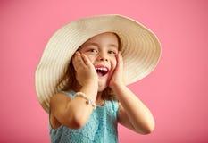 A menina surpreendida no chapéu de palha e no vestido azul, põe suas mãos para enfrentar, expressa a surpresa, abriu sua boca lar foto de stock