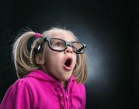 Menina surpreendida pequena em espetáculos grandes engraçados Foto de Stock