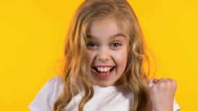 Menina surpreendida que mostra sim o gesto satisfeito com sua vit?ria, fundo amarelo vídeos de arquivo