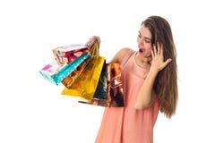 Menina surpreendida que olha os pacotes bonitos brilhantes à disposição isolados no fundo branco Fotografia de Stock Royalty Free